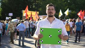 Mens op een vergadering met een banner in zijn handen Plaats voor uw tekst op transponder stock videobeelden