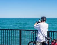 Mens op fiets die foto van Meer Michigan nemen royalty-vrije stock foto's