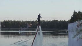 Mens op flyboard De mens in een pak wint het water op een flyboard stock footage