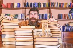 Mens op gelukkig gezicht tussen stapels van boeken, terwijl het bestuderen in bibliotheek, boekenrekken op achtergrond Leraar of  stock fotografie