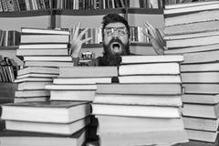 Mens op geschokt gezicht tussen stapels van boeken in bibliotheek, boekenrekken op achtergrond De leraar of de student met baard  stock foto's