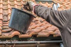 Mens op goten van een ladder de schoonmakende huis royalty-vrije stock afbeeldingen