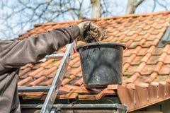 Mens op goten van een ladder de schoonmakende huis stock afbeelding