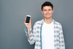 Mens op grijze muur vrije stijl blije die smartphone wordt geïsoleerd van de statusholding stock foto