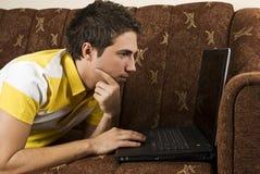 Mens op het bankwerk aangaande laptop Stock Afbeelding
