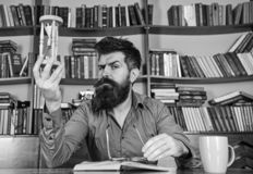 Mens op het bezige boek van de gezichtslezing, boekenrekken op achtergrond Les en tijdconcept Leraar of student met baard royalty-vrije stock afbeeldingen