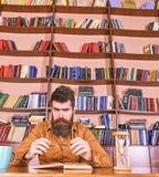 Mens op het bezige boek van de gezichtslezing, boekenrekken op achtergrond Onderwijs en wetenschapsconcept De wetenschapper zit b royalty-vrije stock fotografie