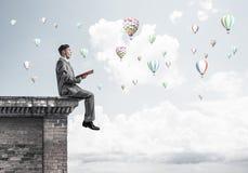 Mens op het boek van de daklezing en aerostaten die in lucht vliegen Royalty-vrije Stock Foto's