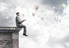 Mens op het boek van de daklezing en aerostaten die in lucht vliegen Stock Afbeeldingen