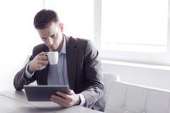 Mens op het bureau die tabletpc met behulp van Royalty-vrije Stock Foto's