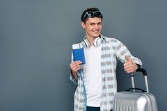 Mens op het grijze concept die van het muurtoerisme zich met het paspoort van de kofferholding met kaartje bevinden die duim tone royalty-vrije stock fotografie