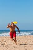 Mens op het strand dat Frisbee speelt Stock Foto's