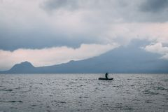Mens op kajak op meer voor berg stock afbeelding