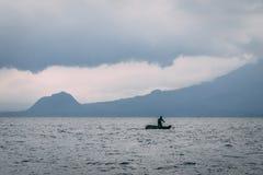 Mens op kajak op meer voor berg stock afbeeldingen