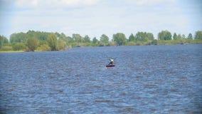 Mens op kiteboard die over de brede rivier vliegen stock footage