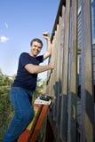 Mens op Ladder - Verticaal stock afbeelding