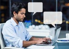 Mens op laptop die laat met lege praatjebellen werken Stock Fotografie