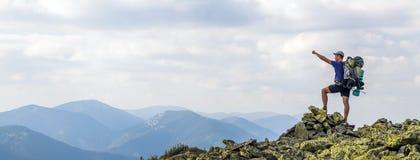 Mens op piek van berg Emotionele scène Jonge mens met backpac Stock Afbeeldingen