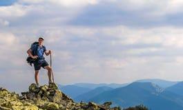 Mens op piek van berg Emotionele scène Jonge mens met backpac royalty-vrije stock foto's