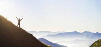 Mens op piek van berg Emotionele scène Jonge mens met backpac stock foto's