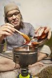 Mens op reis die en in aard ontspannen koken stock afbeelding