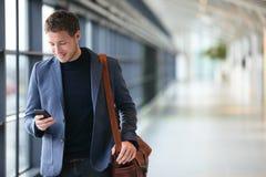 Mens op slimme telefoon - jonge bedrijfsmens in luchthaven royalty-vrije stock afbeelding
