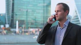 Mens op smartphone - jonge bedrijfsmens die op slimme telefoon spreken Toevallige stedelijke professionele zakenman die mobiele c stock videobeelden