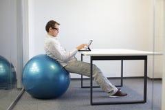 mens op stabiliteitsbal bij bureau Royalty-vrije Stock Afbeeldingen