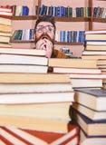 Mens op zenuwachtig gezicht tussen stapels van boeken in bibliotheek, boekenrekken op achtergrond De leraar of de student met baa royalty-vrije stock fotografie