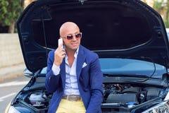 Mens op zijn auto met het open kap gelukkige spreken telefonisch die wordt gesitueerd stock afbeelding