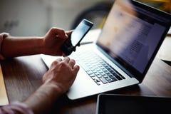 Mens op zijn coworking plaats die technologie gebruiken