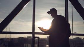 Mens op zonsondergangachtergrond bij de luchthaven die op de telefoon spreken stock footage