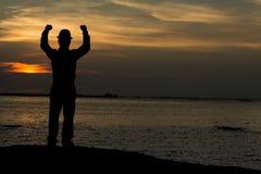 Mens opgeheven wapens op het strand onder de tijd van de zonsondergangschemering royalty-vrije stock foto's