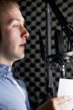 Mens in Opnamestudio die in Microfoon spreken stock fotografie