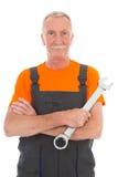 Mens in oranje en grijs globaal met moersleutel Stock Afbeelding