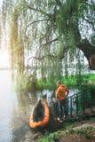 Mens in oranje jasje dichtbij oranje kajak Royalty-vrije Stock Foto