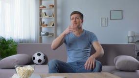Mens over nederlaag van voetbalteam wordt verstoord, het letten op de uitzending van TV, ongelukkige ventilator die stock videobeelden