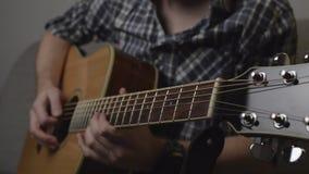 Mens in overhemd het spelen solo op akoestische gitaar met volledige hdlengte van de oogst langzame motie stock videobeelden