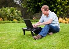 Mens in park dat draadloze laptop computer met behulp van royalty-vrije stock afbeelding