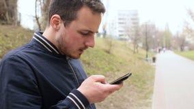 Mens in park met mobiele telefoon stock videobeelden