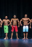 Mens Physique Posing During A Bodybuilding Competition Stock Photos