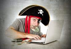 Mens in piraathoed die muziekdossiers en films op computerlaptop downloaden Stock Afbeelding
