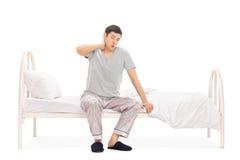 Mens in pyjama'sontwaken met een halspijn stock foto
