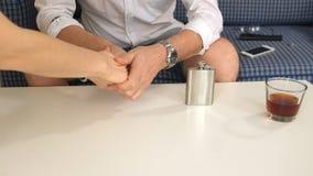 Mens in rechtse fles met alcohol, in linkerverlovingsring denkt, scheiding Close-up stock videobeelden