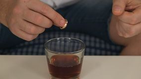 Mens in rechtse fles met alcohol, in linkerverlovingsring denkt, scheiding Close-up stock footage
