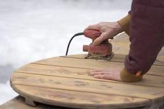 Mens Refinishing een openluchtcederlijst met palmschuurmachine stock foto's