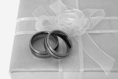Mens rings. Two mens wedding rings arranged on white gift box with white bow Stock Photography