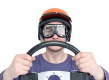 Mens in rode die helm en beschermende brillen met stuurwiel, op witte achtergrond wordt geïsoleerd het concept van de autobestuur stock afbeelding