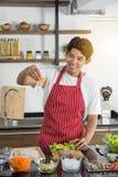 Mens in rode schort die heerlijk en gezond voedsel in de zolderkeuken koken op zonnige dag Het voorbereiden van plantaardige sala stock afbeelding