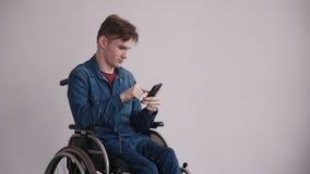 Mens in rolstoel die moderne cellulair thuis gebruiken stock footage